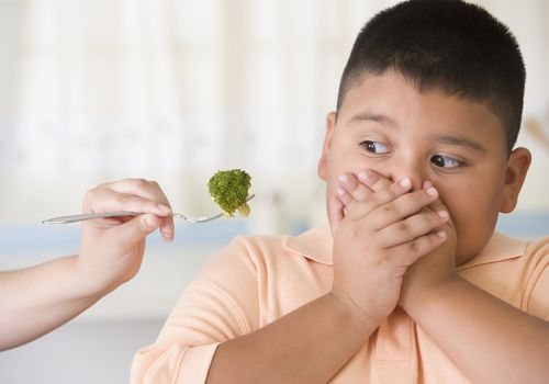 young boy covering mouth as hand tries to feed him broccoli on fork