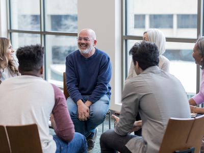 Diverse people sitting in a circle during group therapy