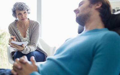 man in therapy session with psychologist