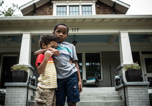 Two young children standing in front of their home