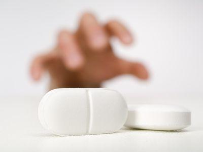Hand desperately reaching for pills.