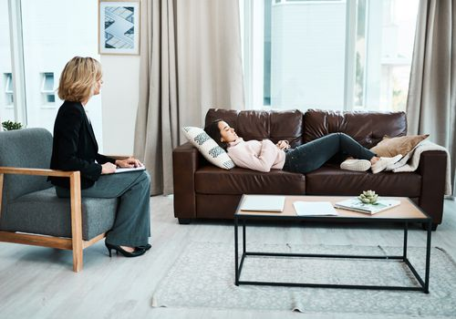 Woman lying on couch in hypnotherapist's office
