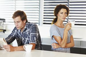 depressed looking man reading at counter and uninterested woman drinking coffee