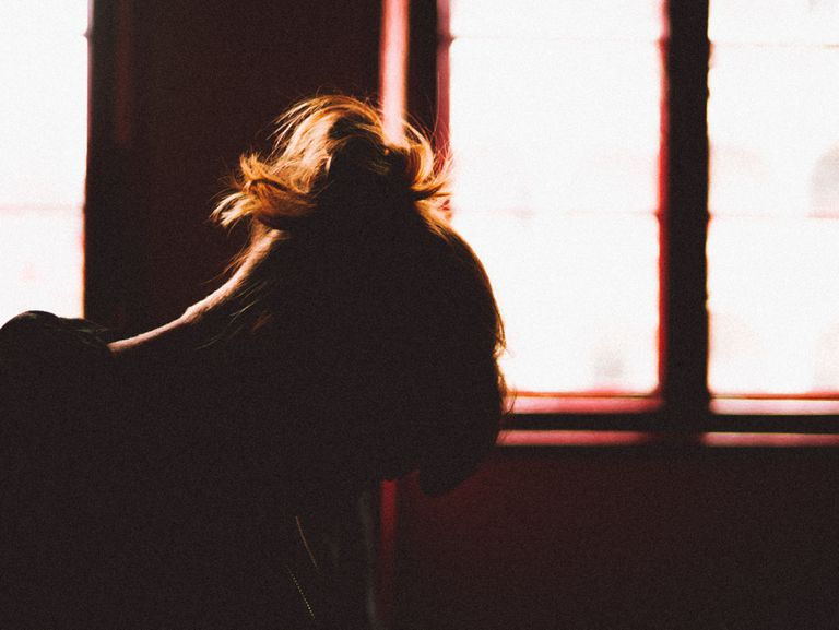 Silhouette of woman with her head down in front of window