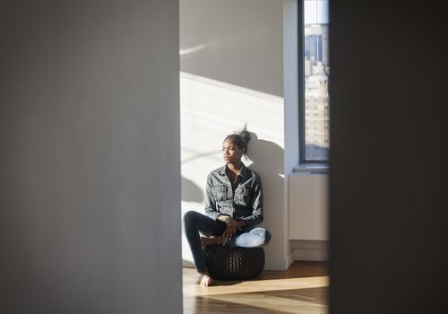 Woman sitting solemnly in hallway
