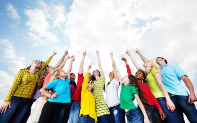group of elementary and middle school children pointing at clouds in sky