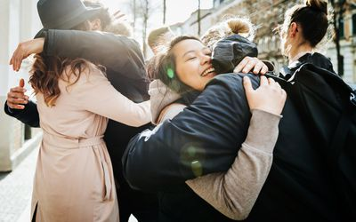 A group of friends meeting up and hugging and smiling with each other before going to a café together.
