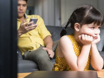 Sad Girl Sitting With Father Looking at Cell Phone