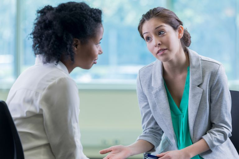 Serious mental health professional talks with patient