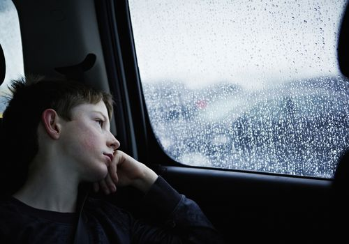 Young boy looking out rainy car window