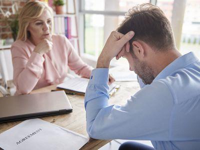 Manager in office reprimanding employee with head in hands
