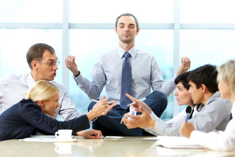 Man meditating on conference table while coworkers argue