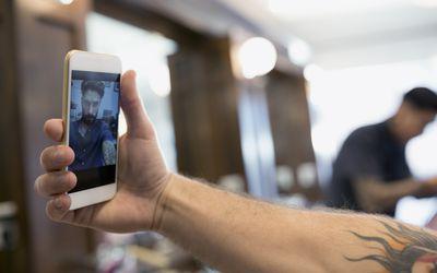 Close up man taking selfie in barber shop