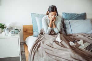 Woman with a cold blowing her nose in bed