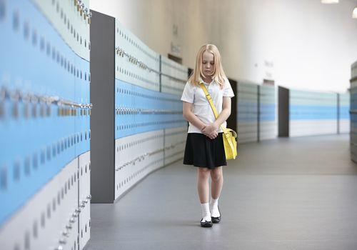 Unhappy schoolgirl walking alone in school corridor