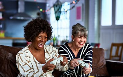 Two middle-aged women smile while holding video game controllers.