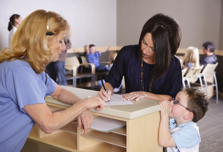 A mom filling out a form about her child at her pediatrician's office.