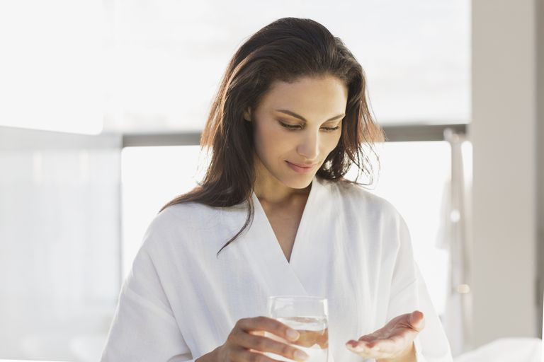 Woman about to take a pill with water