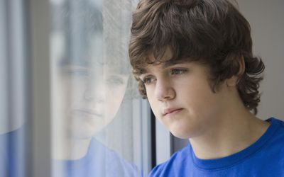 Teenaged boy looking out window