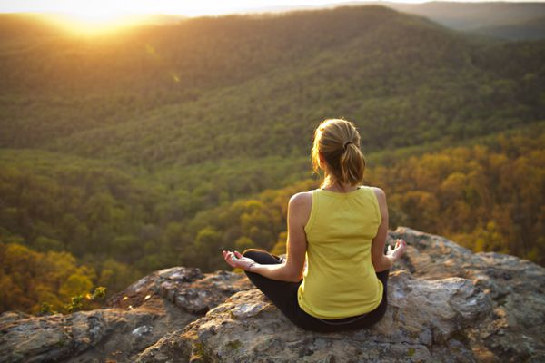 Young woman meditating on mountain
