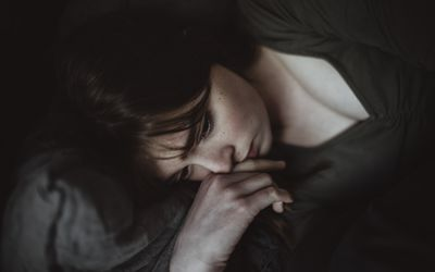 woman lying down with her hand on her face appearing concerned