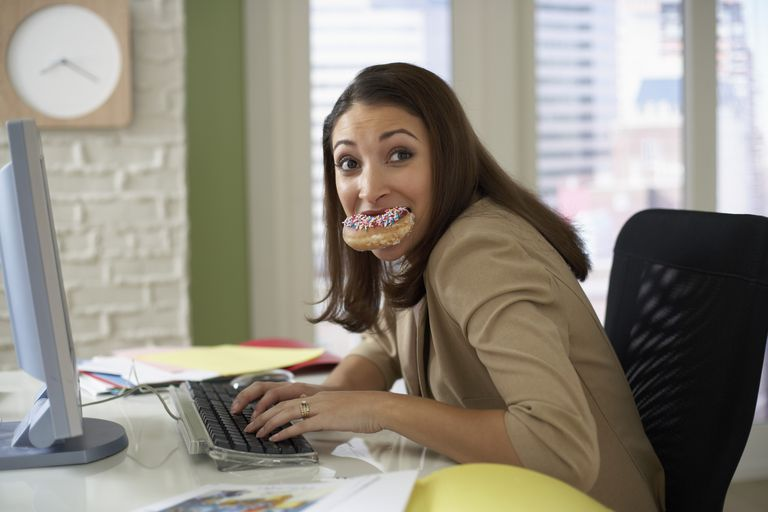 Woman stress eating a donut at her desk