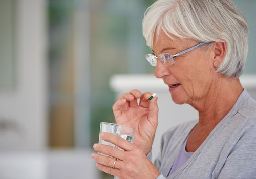 Senior woman taking a pill with water