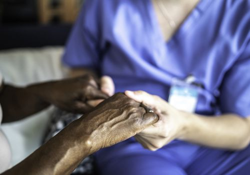 Close-up of home caregiver and senior woman holding hands