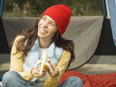 Close-up of a young woman peeling a banana