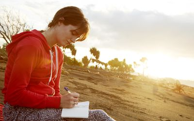 Young woman writing in journal on the beach