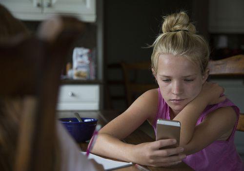 white teen girl looks at her phone
