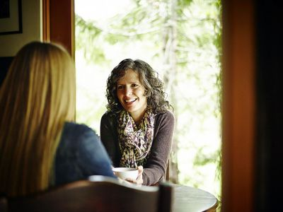 Two mature women in discussion at kitchen table in cabin drinking tea
