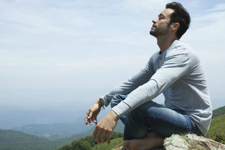 Man meditating on hilltop