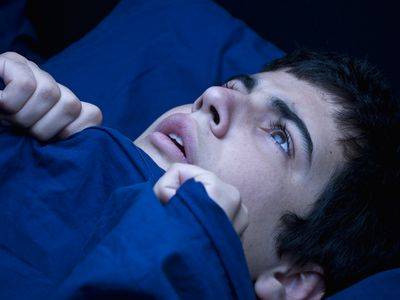 man in bed with blankets pulled up to his chin