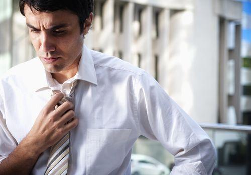 Hispanic businessman loosening necktie in office