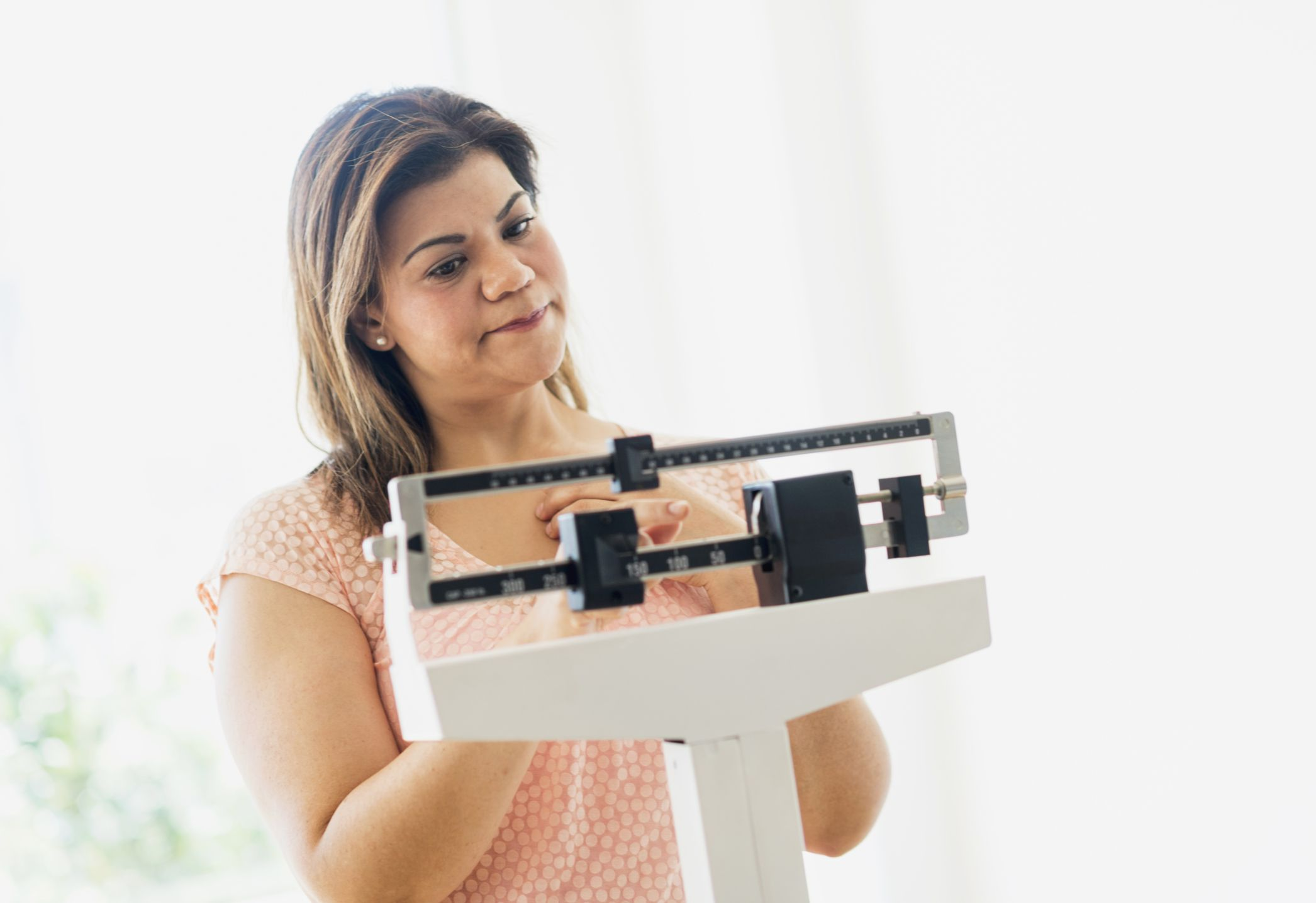 woman frowning on the scale with weight gain