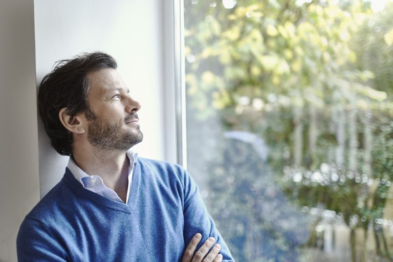 Relaxed man at home looking ot of window