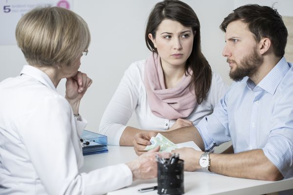 Models pose as worried couple consulting with doctor