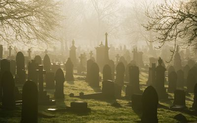 A misty cemetery with many tombstones.