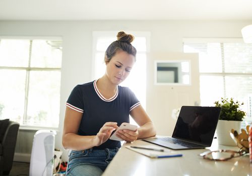 A young woman using a mobile phone while working at home