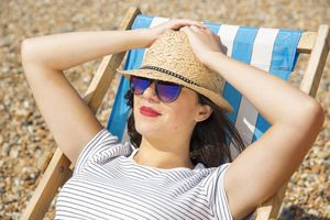 a woman wearing a straw hat and sunglasses sunbathing at the beach on a lounge chair