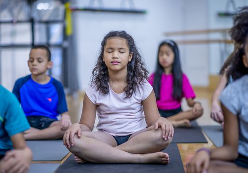 Multi-ethnic group of kids in mindfulness class together.