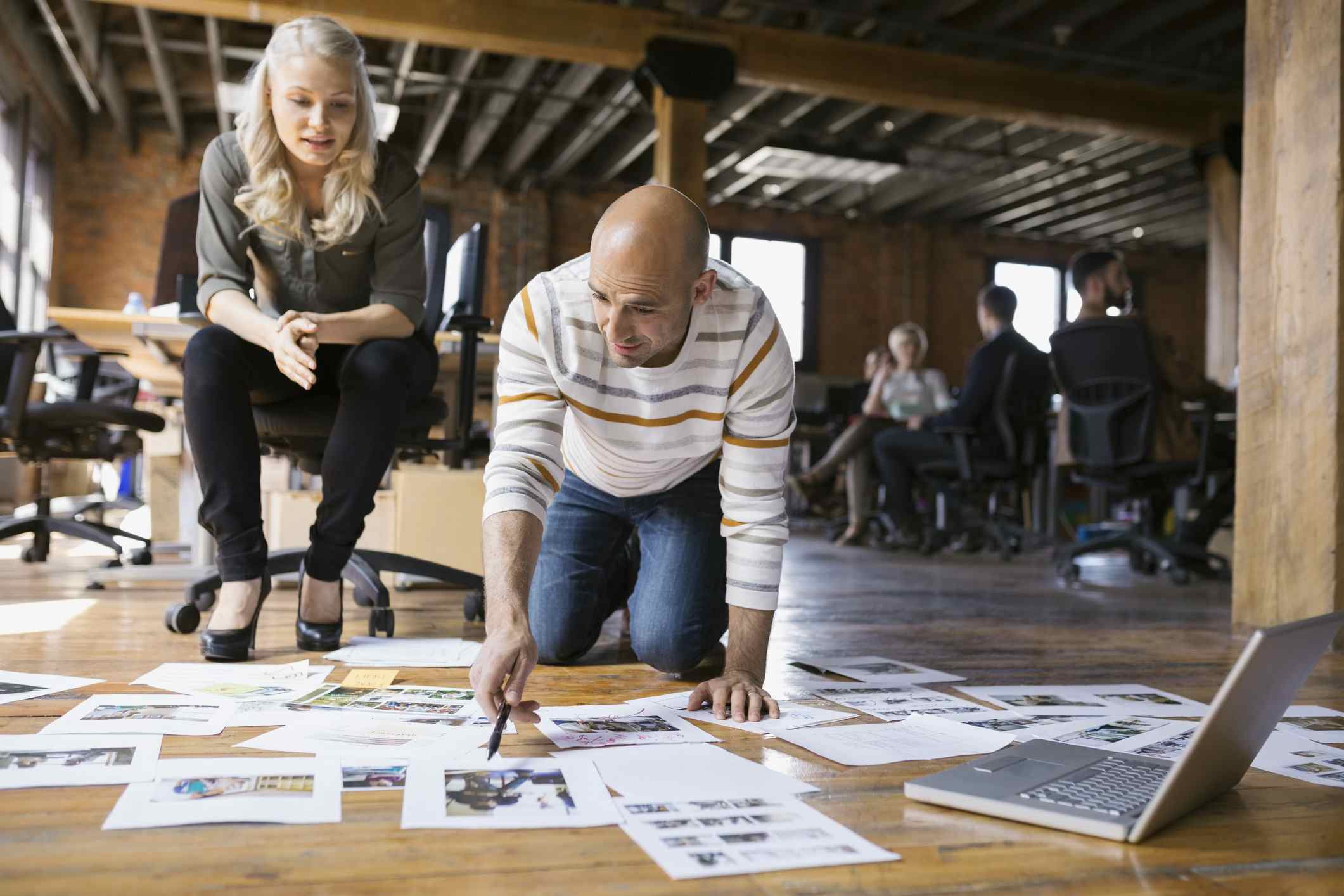Man and woman looking at printed images on the floor of an office