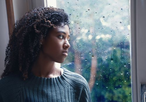 BIPOC woman looking out the window.