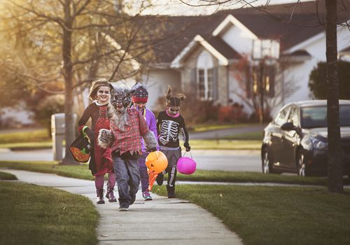 Trick-or-treaters walking down a sidewalk