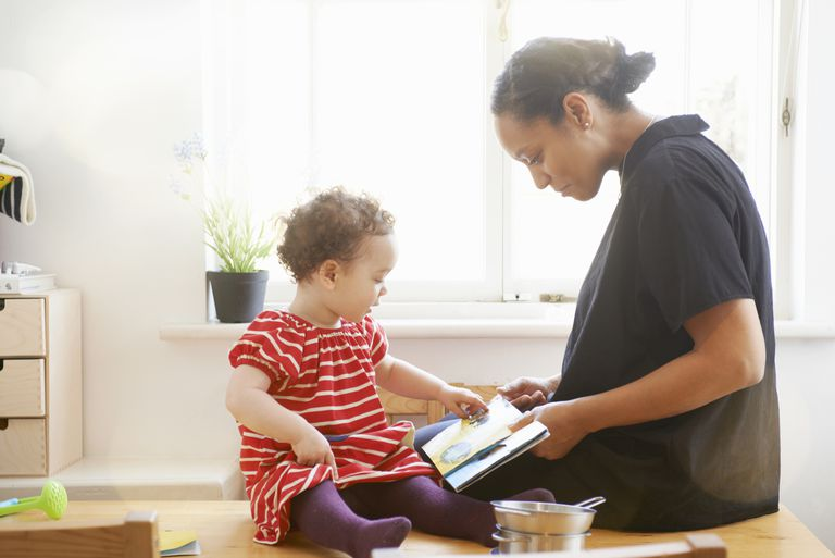 mom showing book to toddler