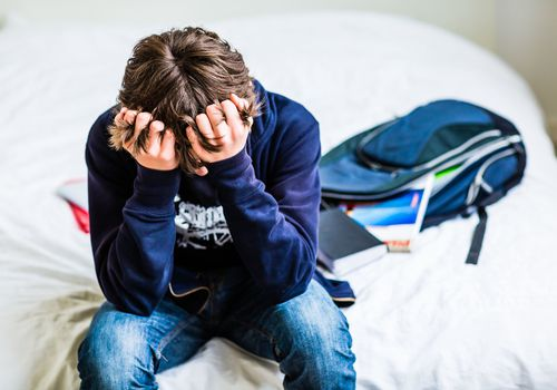Depressed teenage boy sitting on a bed with his head in his hands