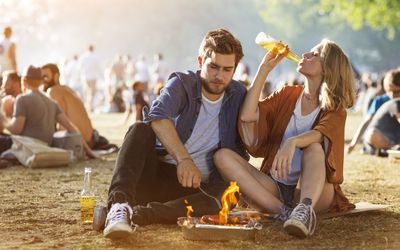 Young couple grilling and drinking beer at outdoor festival