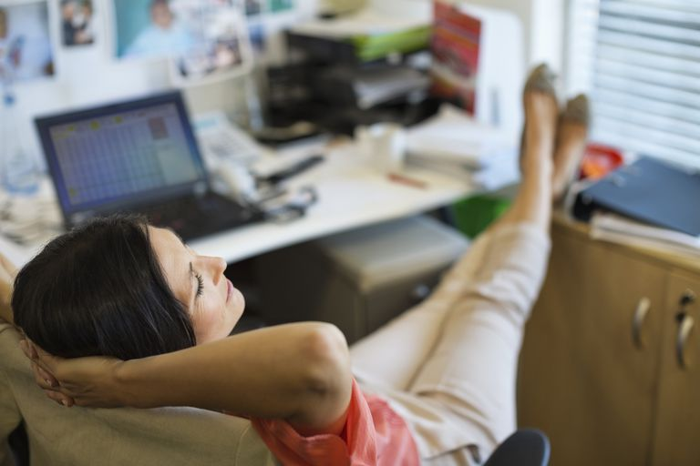 Woman procrastinating at work with feet up on desk