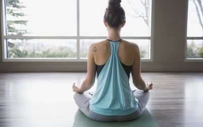 Rear view of woman meditating in lotus position